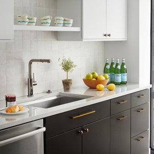 シカゴの中くらいのエクレクティックスタイルのおしゃれなアイランドキッチン (アンダーカウンターシンク、フラットパネル扉のキャビネット、珪岩カウンター、白いキッチンパネル、テラコッタタイルのキッチンパネル、シルバーの調理設備、無垢フローリング、茶色い床、グレーのキッチンカウンター) の写真