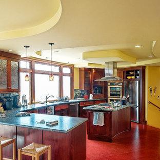 サンフランシスコの中くらいのエクレクティックスタイルのおしゃれなキッチン (ダブルシンク、濃色木目調キャビネット、青いキッチンパネル、ガラスタイルのキッチンパネル、シルバーの調理設備、落し込みパネル扉のキャビネット、大理石カウンター、リノリウムの床、赤い床) の写真