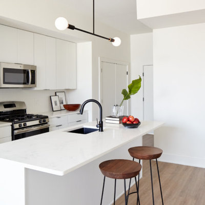 Example of a small trendy galley light wood floor and beige floor open concept kitchen design in Philadelphia with an undermount sink, flat-panel cabinets, white cabinets, quartz countertops, white backsplash, ceramic backsplash, stainless steel appliances and an island