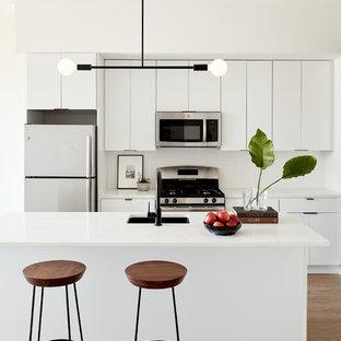 Modelo de cocina contemporánea, pequeña, con fregadero bajoencimera, armarios con paneles lisos, puertas de armario blancas, encimera de cuarzo compacto, salpicadero blanco, electrodomésticos de acero inoxidable, suelo de madera clara, una isla y suelo beige