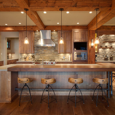 Inspiration for a large rustic galley medium tone wood floor kitchen remodel in Vancouver with shaker cabinets, light wood cabinets, wood countertops, stainless steel appliances, stone tile backsplash and an island