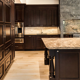 Design ideas for a large classic u-shaped kitchen/diner in Miami with a built-in sink, raised-panel cabinets, dark wood cabinets, granite worktops, white splashback, stone tiled splashback, stainless steel appliances, porcelain flooring, an island and beige floors.