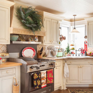 Photo of a country kitchen in Other with a drop-in sink, raised-panel cabinets, beige cabinets, tile benchtops, beige splashback, stainless steel appliances, dark hardwood floors, brown floor and beige benchtop.