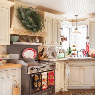 Landhaus Küche mit Einbauwaschbecken, profilierten Schrankfronten, beigen Schränken, Arbeitsplatte aus Fliesen, Küchenrückwand in Beige, Küchengeräten aus Edelstahl, dunklem Holzboden, braunem Boden und beiger Arbeitsplatte in Sonstige