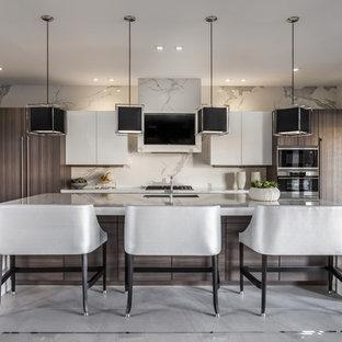 マイアミの広いコンテンポラリースタイルのおしゃれなアイランドキッチン (フラットパネル扉のキャビネット、大理石カウンター、白いキッチンパネル、大理石のキッチンパネル、シルバーの調理設備、セラミックタイルの床、白いキッチンカウンター、アンダーカウンターシンク、白いキャビネット、グレーの床) の写真