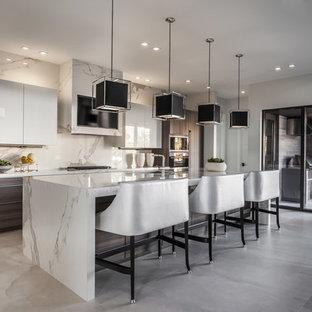 マイアミの大きいコンテンポラリースタイルのおしゃれなキッチン (シングルシンク、フラットパネル扉のキャビネット、中間色木目調キャビネット、大理石カウンター、白いキッチンパネル、大理石の床、シルバーの調理設備の、セラミックタイルの床、白い床、白いキッチンカウンター) の写真