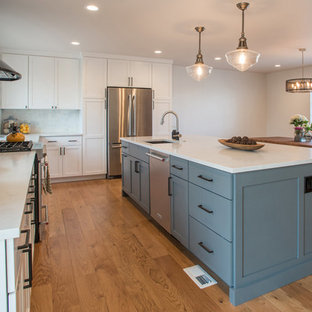 This is an example of a mid-sized contemporary galley eat-in kitchen in Denver with an undermount sink, glass-front cabinets, beige cabinets, quartz benchtops, white splashback, ceramic splashback, stainless steel appliances, medium hardwood floors and with island.