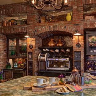 オーランドの中サイズの地中海スタイルのおしゃれなキッチン (エプロンフロントシンク、御影石カウンター、カラー調理設備、トラバーチンの床、レイズドパネル扉のキャビネット、中間色木目調キャビネット、マルチカラーのキッチンパネル、セメントタイルのキッチンパネル) の写真