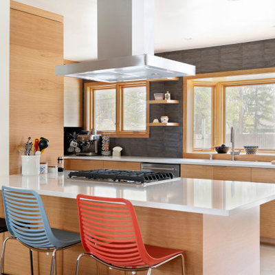 Small mid-century modern galley porcelain tile and gray floor eat-in kitchen photo in Minneapolis with an undermount sink, flat-panel cabinets, light wood cabinets, quartzite countertops, gray backsplash, subway tile backsplash, stainless steel appliances, an island and white countertops