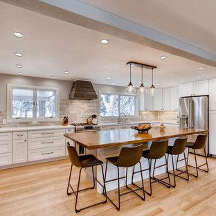 Inredning av ett klassiskt stort vit vitt kök, med en undermonterad diskho, skåp i shakerstil, vita skåp, bänkskiva i kvarts, flerfärgad stänkskydd, stänkskydd i porslinskakel, rostfria vitvaror, ljust trägolv, en köksö och gult golv