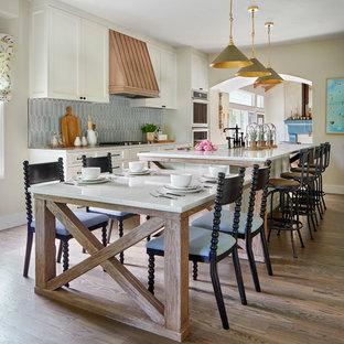 Bild på ett stort lantligt vit vitt kök, med en dubbel diskho, vita skåp, bänkskiva i koppar, blått stänkskydd, stänkskydd i porslinskakel, rostfria vitvaror, mellanmörkt trägolv, en köksö, brunt golv och skåp i shakerstil