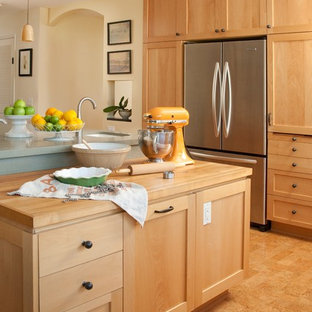Inspiration for a large traditional l-shaped eat-in kitchen in Santa Barbara with stainless steel appliances, light wood cabinets and an island.