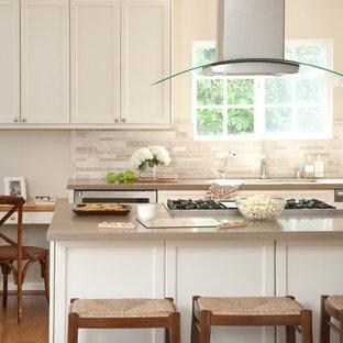 Idée de décoration pour une grande cuisine tradition avec un plan de travail en quartz modifié, des portes de placard blanches, une crédence beige, un électroménager en acier inoxydable, un sol en bois brun, un îlot central et une crédence en travertin.