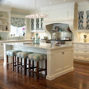 Imagen de cocina tradicional con puertas de armario beige, electrodomésticos de acero inoxidable, salpicadero metalizado, salpicadero de metal y armarios tipo vitrina