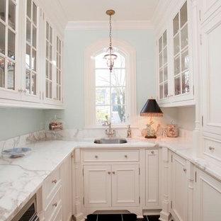 Inredning av ett klassiskt litet vit vitt kök, med en rustik diskho, släta luckor, vita skåp, marmorbänkskiva, vitt stänkskydd, stänkskydd i tunnelbanekakel, rostfria vitvaror, klinkergolv i keramik och svart golv