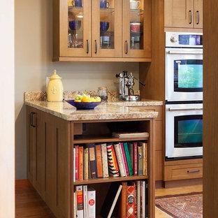 Ejemplo de cocina en U, clásica renovada, de tamaño medio, abierta, con fregadero bajoencimera, armarios estilo shaker, puertas de armario de madera oscura, encimera de granito, salpicadero amarillo, electrodomésticos de acero inoxidable, suelo de madera en tonos medios y península