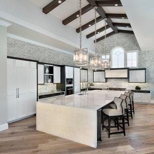 Пример оригинального дизайна: огромная угловая кухня в стиле современная классика с белыми фасадами, фартуком из плитки мозаики, техникой под мебельный фасад, светлым паркетным полом, островом, врезной раковиной, фасадами в стиле шейкер, разноцветным фартуком, обеденным столом и столешницей из оникса