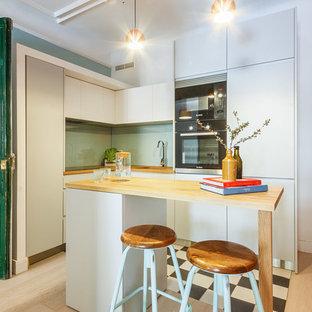 Ejemplo de cocina en L, actual, de tamaño medio, con armarios con paneles lisos, encimera de madera, una isla, puertas de armario grises, salpicadero gris, salpicadero de vidrio templado, electrodomésticos negros y suelo de madera clara