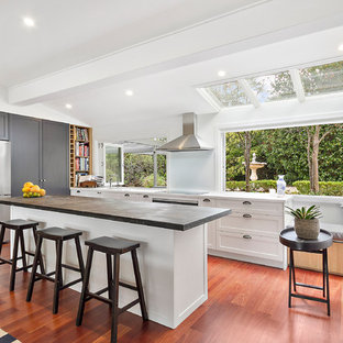 This is an example of an expansive contemporary l-shaped open plan kitchen in Sydney with brown floor, shaker cabinets, with island, an integrated sink, white cabinets, zinc benchtops, white splashback, glass sheet splashback, black appliances, light hardwood floors and grey benchtop.