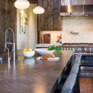 Idées déco pour une grande cuisine américaine montagne en L avec un évier encastré, un placard à porte shaker, des portes de placard marrons, un plan de travail en calcaire, une crédence jaune, une crédence en carreau de terre cuite, un électroménager en acier inoxydable, un sol en bois foncé, un îlot central et un sol marron.
