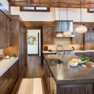 Modelo de cocina rural con fregadero bajoencimera, armarios estilo shaker, puertas de armario de madera en tonos medios, salpicadero multicolor, electrodomésticos de acero inoxidable, suelo de madera oscura y una isla