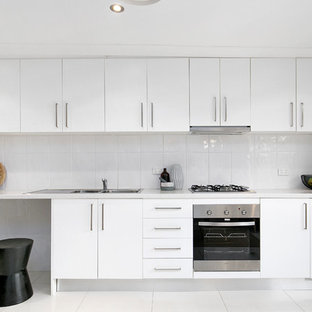Photo of a contemporary single-wall kitchen in Sydney with a double-bowl sink, flat-panel cabinets, white cabinets, quartz benchtops, white splashback, ceramic splashback, stainless steel appliances, ceramic floors, no island, white floor and white benchtop.