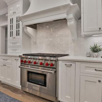 Inspiration for a large timeless u-shaped light wood floor and multicolored floor eat-in kitchen remodel in Boston with a farmhouse sink, beaded inset cabinets, white cabinets, quartz countertops, white backsplash, marble backsplash, stainless steel appliances, an island and white countertops