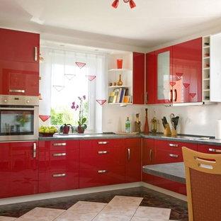 Foto di una cucina minimalista di medie dimensioni con lavello da incasso, ante di vetro, ante rosse, top in cemento, isola, pavimento multicolore e top grigio