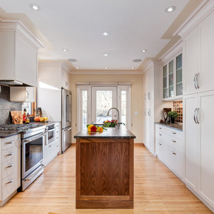 Design ideas for a traditional galley kitchen pantry in Calgary with a built-in sink, shaker cabinets, white cabinets, granite worktops, orange splashback, stainless steel appliances, light hardwood flooring and an island.