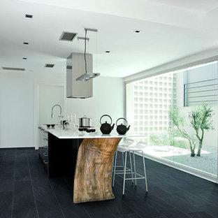 マイアミのアジアンスタイルのおしゃれなアイランドキッチン (アンダーカウンターシンク、人工大理石カウンター、磁器タイルの床、黒い床) の写真