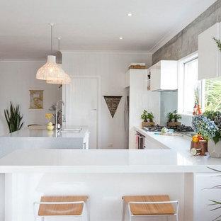 Inredning av ett skandinaviskt stort kök, med en dubbel diskho, släta luckor, vita skåp, bänkskiva i kvarts, vitt stänkskydd, stänkskydd i glaskakel, rostfria vitvaror, ljust trägolv och en köksö