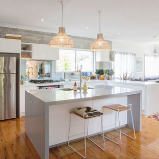 Large scandinavian l-shaped eat-in kitchen in Other with flat-panel cabinets, white cabinets, stainless steel appliances, light hardwood floors, with island, a double-bowl sink, quartz benchtops, white splashback and glass tile splashback.