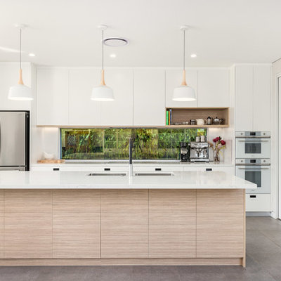 Example of a small trendy galley porcelain tile and gray floor eat-in kitchen design in Sydney with an undermount sink, flat-panel cabinets, white cabinets, window backsplash, white appliances, an island, white countertops and quartz countertops