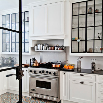 Inspiration for a contemporary l-shaped enclosed kitchen remodel in Los Angeles with a farmhouse sink, glass-front cabinets, white cabinets, stainless steel appliances, soapstone countertops and white backsplash