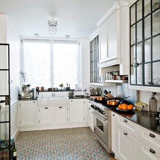 ロサンゼルスのコンテンポラリースタイルのおしゃれなキッチン (エプロンフロントシンク、ガラス扉のキャビネット、白いキャビネット、シルバーの調理設備、ソープストーンカウンター) の写真