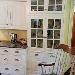 Modelo de cocina comedor en L, tradicional, pequeña, sin isla, con fregadero bajoencimera, armarios con rebordes decorativos, puertas de armario blancas, encimera de cuarzo compacto, salpicadero amarillo, electrodomésticos de acero inoxidable y suelo de madera clara