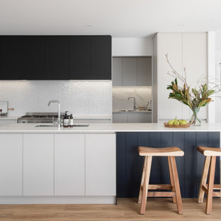 This is an example of a contemporary kitchen in Hobart with an undermount sink, flat-panel cabinets, white cabinets, white splashback, stainless steel appliances, light hardwood floors, with island and white benchtop.