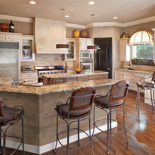 Traditional kitchen pictures - Elegant kitchen photo in Dallas with raised-panel cabinets, beige cabinets, beige backsplash, stone tile backsplash, stainless steel appliances and beige countertops