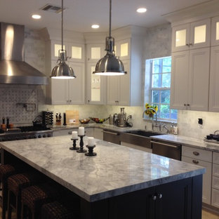Large traditional kitchen ideas - Large elegant u-shaped travertine floor and beige floor kitchen photo in Miami with a farmhouse sink, recessed-panel cabinets, white cabinets, marble countertops, white backsplash, stainless steel appliances, an island and stone tile backsplash