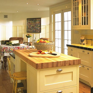 This is an example of a mid-sized traditional u-shaped eat-in kitchen in San Francisco with a farmhouse sink, white cabinets, tile benchtops, yellow splashback, ceramic splashback, stainless steel appliances, medium hardwood floors, with island, shaker cabinets and yellow benchtop.