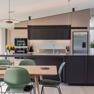 Photo of a contemporary eat-in kitchen in Hamilton with an integrated sink, flat-panel cabinets, brown cabinets, stainless steel benchtops, white splashback, stainless steel appliances, light hardwood floors, with island and beige floor.