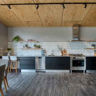 This is an example of a mid-sized contemporary single-wall eat-in kitchen in Christchurch with a drop-in sink, flat-panel cabinets, black cabinets, stainless steel benchtops, white splashback, ceramic splashback, stainless steel appliances, vinyl floors, no island, grey floor and grey benchtop.