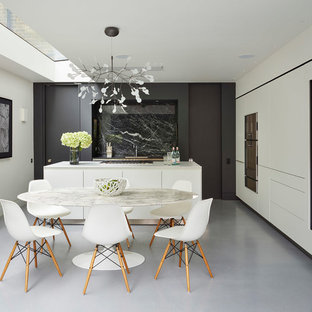 Inspiration for a contemporary kitchen in London with flat-panel cabinets, white cabinets, black splashback, stone slab splashback, concrete flooring, an island and grey floors.