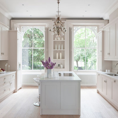 Inspiration for a transitional kitchen remodel in London with recessed-panel cabinets, white cabinets, white backsplash, glass sheet backsplash and paneled appliances