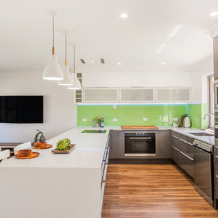 Design ideas for a contemporary u-shaped open plan kitchen in Perth with an undermount sink, flat-panel cabinets, grey cabinets, green splashback, glass sheet splashback, stainless steel appliances, dark hardwood floors, a peninsula and white benchtop.
