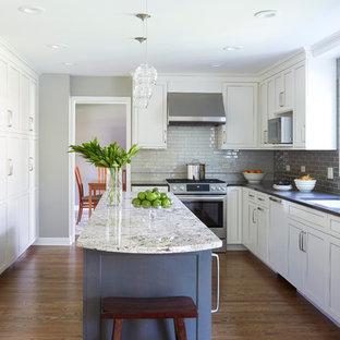 Inredning av ett klassiskt mellanstort, avskilt l-kök, med vita skåp, bänkskiva i kvarts, grått stänkskydd, rostfria vitvaror, en köksö, en undermonterad diskho, stänkskydd i glaskakel, mörkt trägolv och luckor med infälld panel