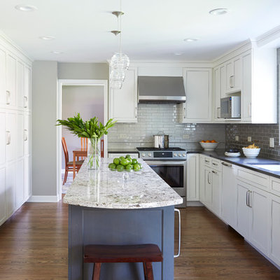 Enclosed kitchen - mid-sized transitional l-shaped dark wood floor enclosed kitchen idea in Chicago with white cabinets, quartz countertops, gray backsplash, stainless steel appliances, an island, an undermount sink, glass tile backsplash and recessed-panel cabinets