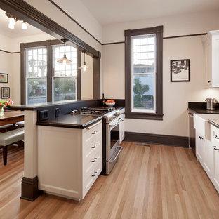 サンタバーバラの小さいヴィクトリアン調のおしゃれなキッチン (エプロンフロントシンク、落し込みパネル扉のキャビネット、白いキャビネット、御影石カウンター、黒いキッチンパネル、シルバーの調理設備の、淡色無垢フローリング) の写真