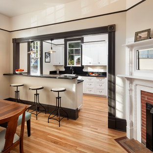 This is an example of a small traditional galley eat-in kitchen in Santa Barbara with recessed-panel cabinets, white cabinets, granite benchtops, black splashback, light hardwood floors, stainless steel appliances and a farmhouse sink.