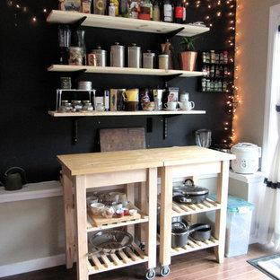 Diseño de cocina comedor de galera, ecléctica, pequeña, con armarios abiertos, puertas de armario de madera clara, encimera de madera, salpicadero negro, suelo de madera oscura y dos o más islas